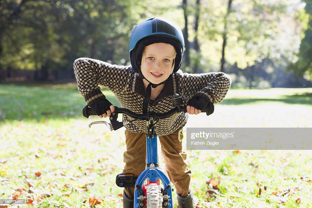 portrait of little boy holding his bicycle : Stock Photo