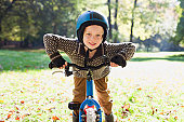 portrait of little boy holding his bicycle