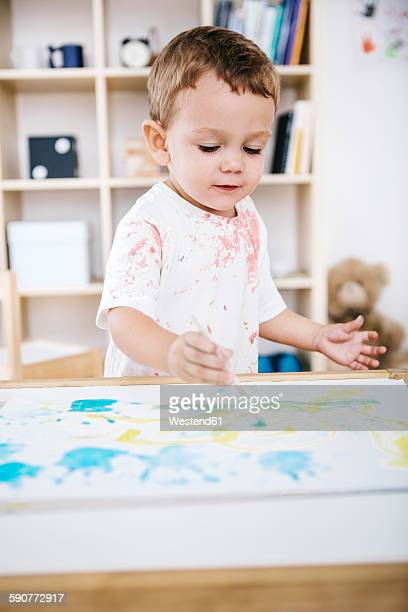 Portrait of little boy painting with watercolours