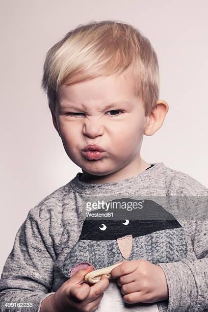Portrait of little boy pouting a mouth