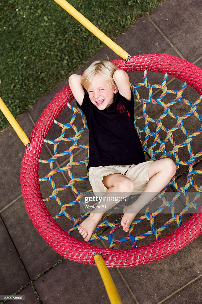 Portrait of little boy relaxing on a playground equipment