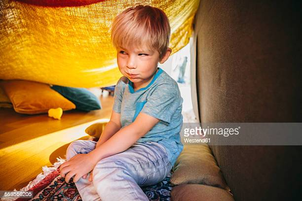 Portrait of little boy sitting in a blanket cave making a funny face