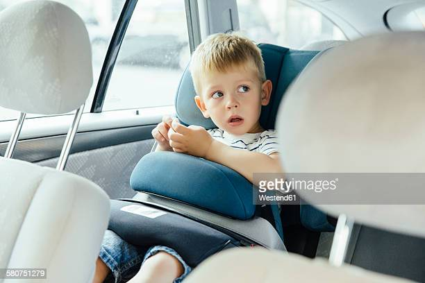 Portrait of little boy sitting in his car seat