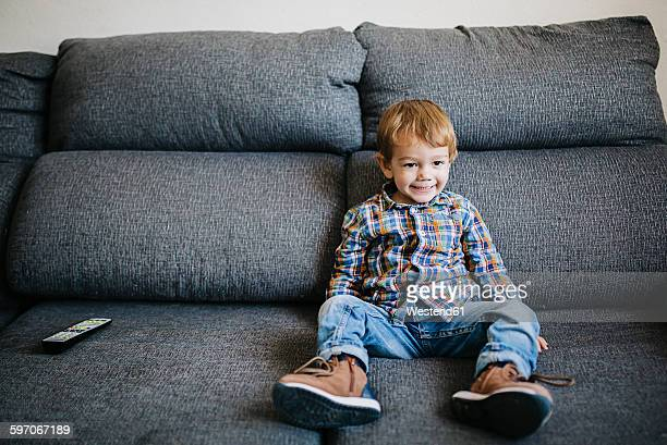 Portrait of little boy sitting on the couch watching TV