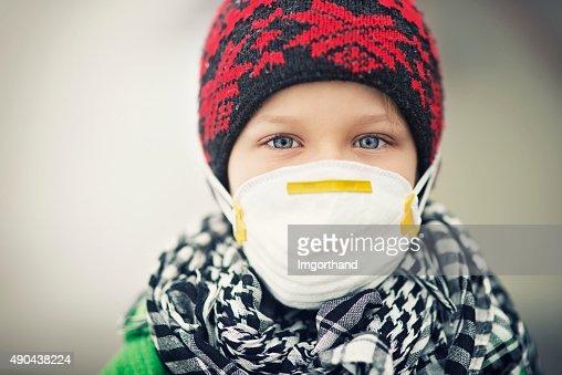Portrait of little boy wearing pollution mask