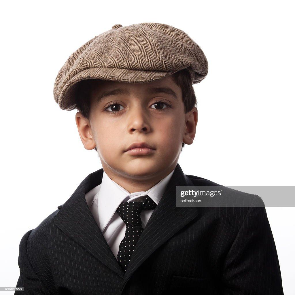 Portrait of little boy wearing striped suit and flat cap