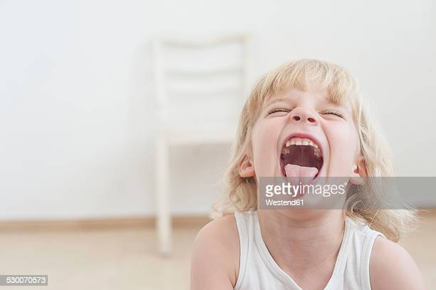 Portrait of little boy with outstretched tongue