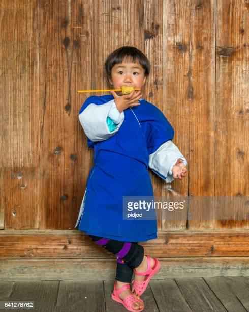 Portrait of little girl eating corn on the cob