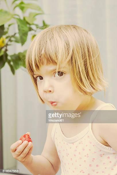 Portrait of little girl eating strawberry