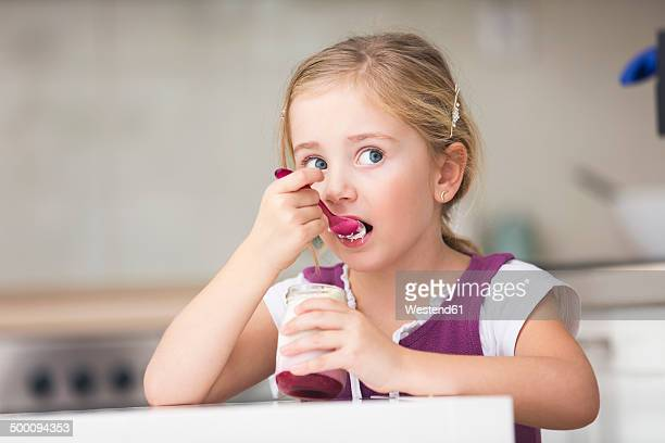 Portrait of little girl eating yogurt