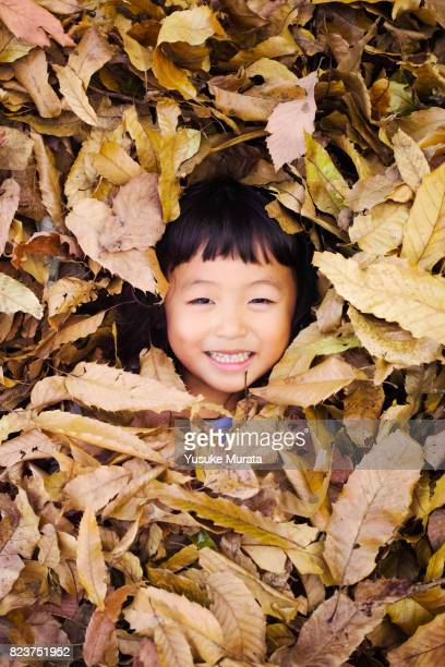 Portrait of little girl in fall leaves