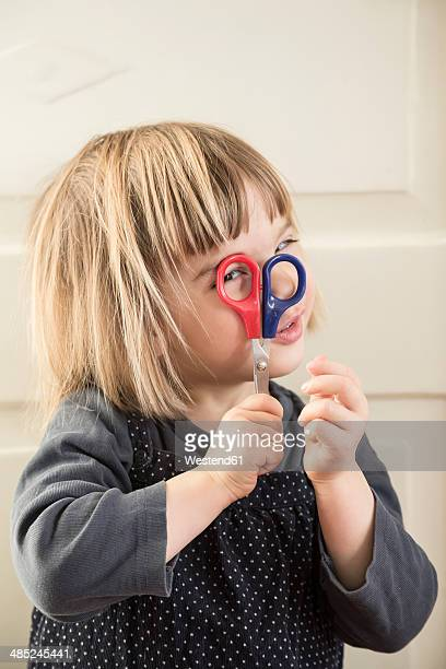 Portrait of little girl looking through the handle of scissors