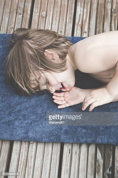 Portrait of little girl lying on towel on balcony