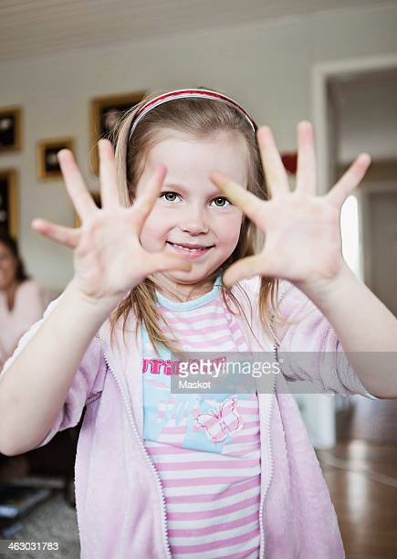 Portrait of little girl showing open palms at home