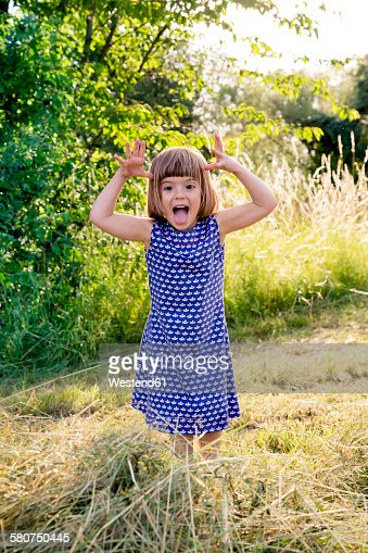 Portrait of little girl standing in hay field making faces