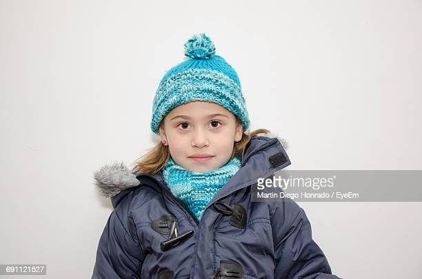 Portrait Of Little Girl Wearing Warm Clothes Against White Background