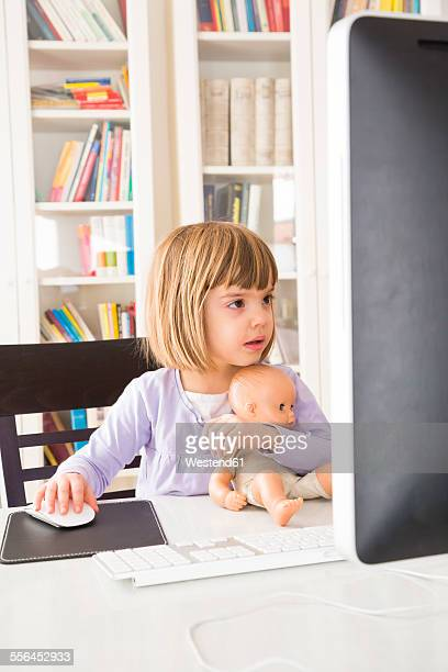 Portrait of little girl with doll spending time at computer