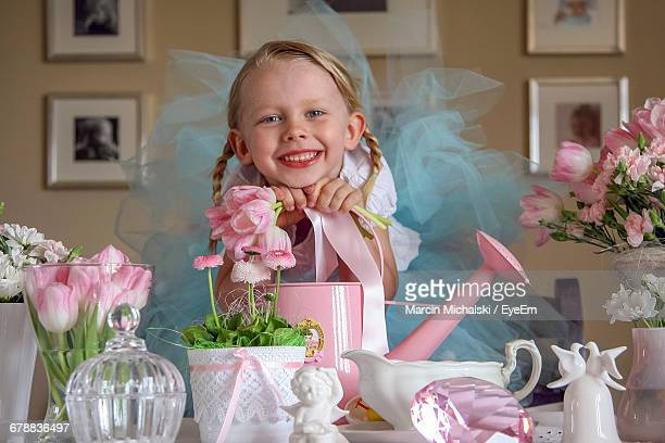 Portrait Of Little Girl With Objects On Table