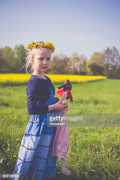 Portrait of little girl with soft toy in front of rape field