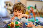 Portrait of little kid boy sad on birthday. child with lots of toys. Tired preschool boy
