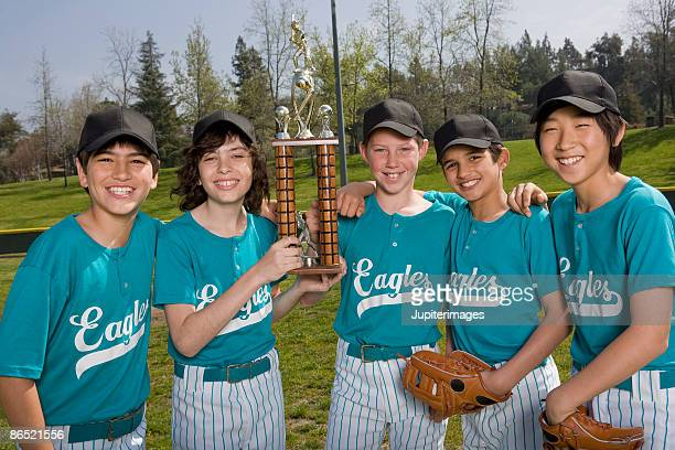 Portrait of little league players with trophy