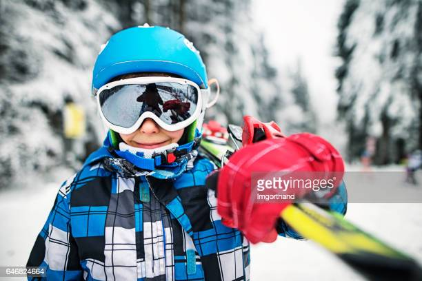 Portrait of little skier with skis