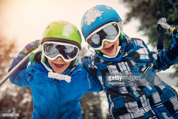 Portret van weinig skiërs lachen om de camera