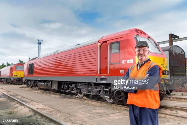 Portrait of locomotive engineer by locomotive in train works