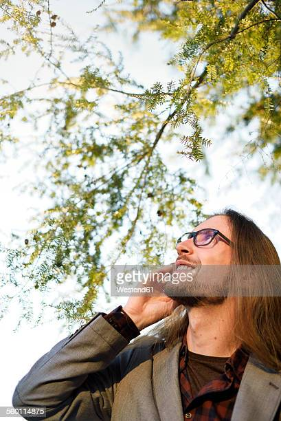 Portrait of long-haired hipster telephoning with smartphone