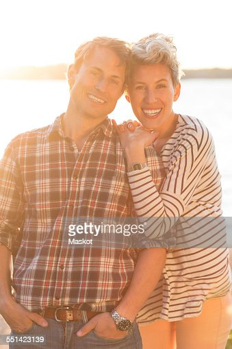 Portrait of loving couple standing on beach during sunset