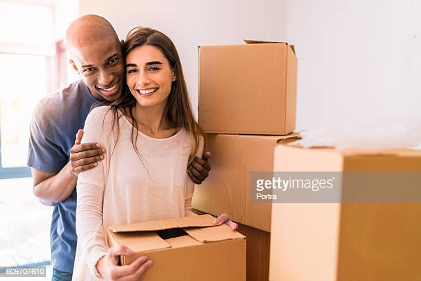 Portrait of loving couple with boxes in new house