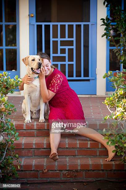 portrait of loving girl and her dog on front porch