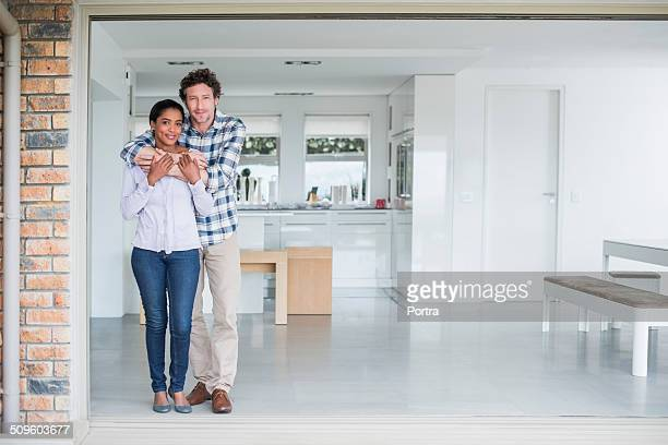 Portrait of loving man embracing woman at home