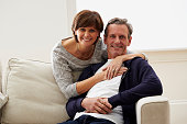 Portrait of loving mature couple together at home looking at camera