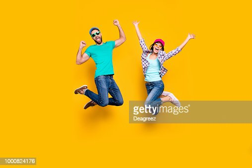 Portrait of lucky successful couple jumping with raised fists celebrating victory wearing denim outfit isolated on bright yellow background. Energy luck success concept : Stock Photo
