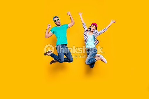 Portrait of lucky successful couple jumping with raised fists celebrating victory wearing denim outfit isolated on bright yellow background. Energy luck success concept : Foto de stock