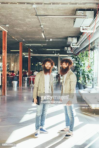 Portrait of male adult hipster twins holding digital tablet and laptop in office