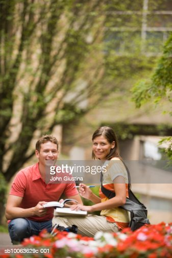 Portrait of male and female students with books on campus outdoors, smiling : Stock Photo