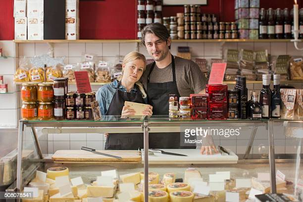 Portrait of male and female worker standing at display cabinet in supermarket
