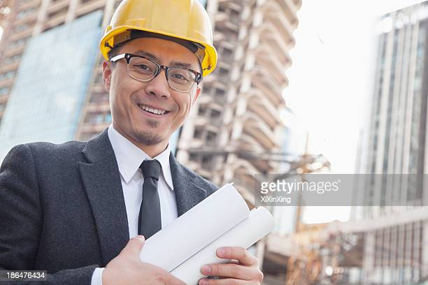 Portrait of male architect on site carrying blueprints