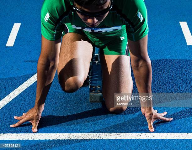 portrait of male athlete in starting blocks