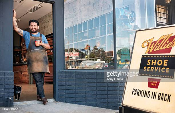 Portrait of male cobbler leaning against shoe shop doorway
