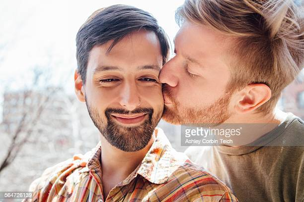 Portrait of male couple, mid adult man kissing his partners cheek
