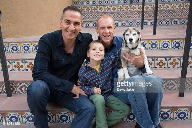 Portrait of male couple, son and dog sitting on stairs in park
