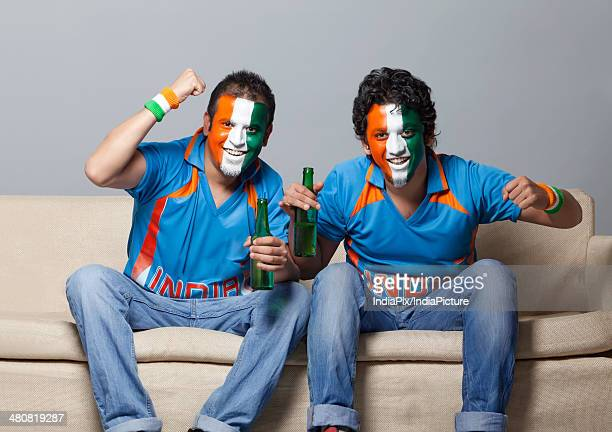 Portrait of male cricket fans with face painted in Indian tricolor cheering while having drink at home