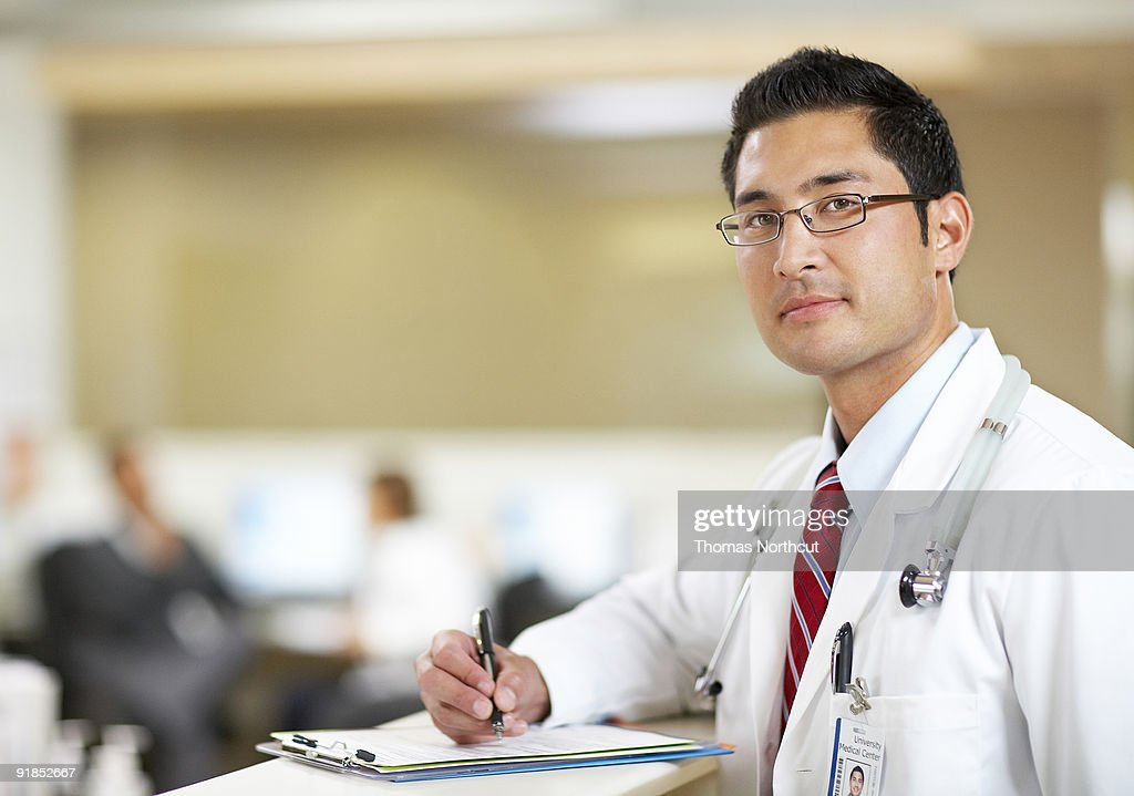 Portrait of male doctor at nurse's station : Stock Photo