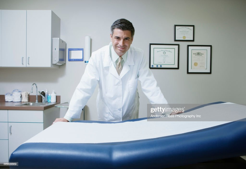 Portrait of male doctor leaning on examination table in clinic : Stock Photo