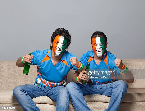 Portrait of male friends on sofa with painted face cheering while having beer at home
