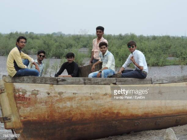 Portrait Of Male Friends Sitting On Boot Moored At Riverbank