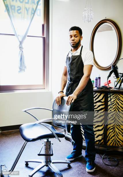 Portrait of male hair stylist by chair in salon